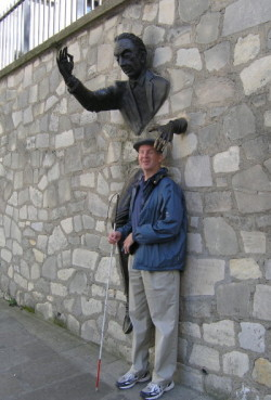 Mike standing with his head cradled by the Bronze man