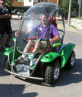 Mike driving the Otto Bock, huge smile on his face with his cane sticking out the front