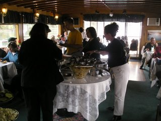 The interior view of the Willamette Queen, the buffet table in the middle and guests seated along the windowed edge