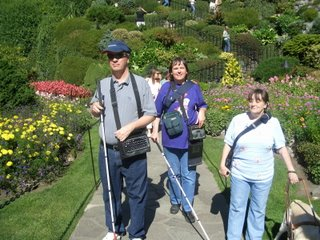 Paul, Kathy, Ilona make their way down a pathway in the gardens, behind them is a zig-zagging staircase.  Everything is surrounded in greenery and blooming flowers