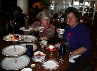 Sheila enjoying high tea, the spread on the table is impressive.  The teacups are fine china, there is a three tiered dessert tray with assorted goodies on it, there are fresh fruit cups with a dollup of shipped cream on top,