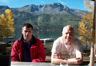 Tech support in action: Chris and Gil sitting at a picnic table with the lake and mountains in the background