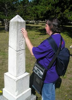 Ilona looking at a tombstone with Japanese/Chinese characters