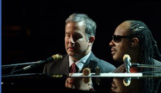 Mike and Stevie Wonder on stage sitting at a piano during the house Full of Toys Concert