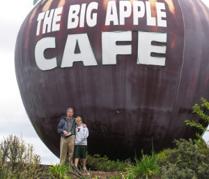 Mike and Wyndham in front of the Big Apple Cafe in New Zealand, the structure of the cafe is a huge apple